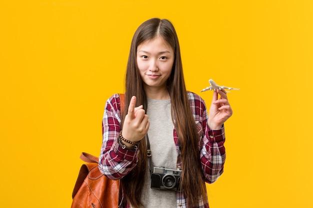Jovem mulher asiática segurando um ícone de avião apontando com o dedo para você como se fosse um convite para se aproximar. Foto Premium