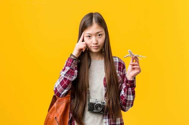 Jovem mulher asiática segurando um ícone de avião apontando seu templo com o dedo, pensando, focado em uma tarefa.