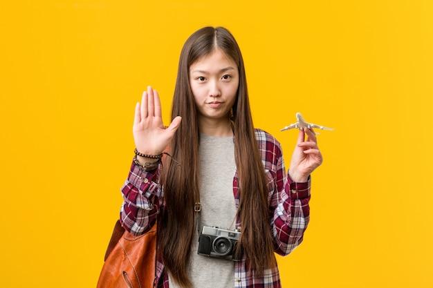 Jovem mulher asiática segurando um ícone de avião em pé com a mão estendida, mostrando o sinal de stop, impedindo-o.