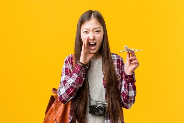Jovem mulher asiática segurando um ícone de avião gritando animado para a frente