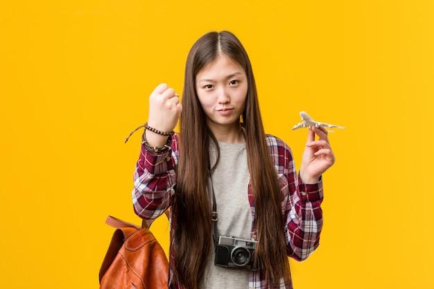 Jovem mulher asiática segurando um ícone de avião, mostrando o punho para a câmera, expressão facial agressiva.