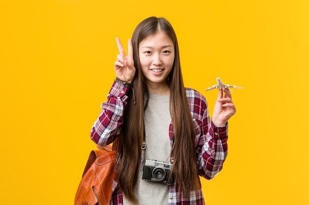 Jovem mulher asiática segurando um ícone de avião mostrando sinal de vitória e sorrindo amplamente. Foto Premium