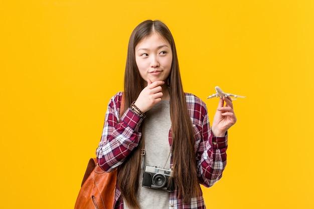 Jovem mulher asiática segurando um ícone de avião, olhando de soslaio com expressão duvidosa e cética.