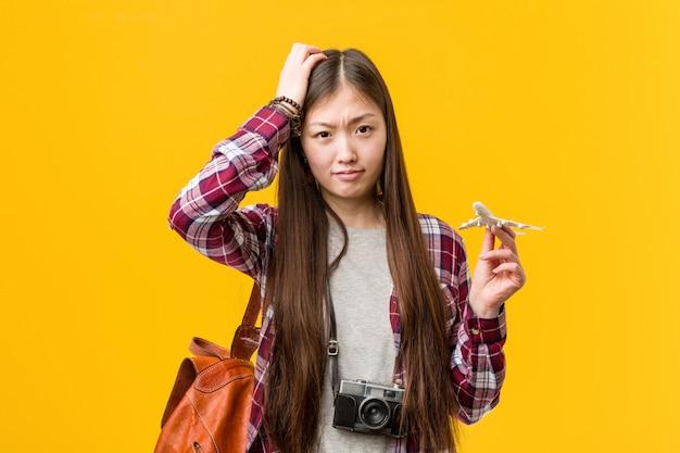 Jovem mulher asiática segurando um ícone de avião sendo chocado, ela se lembrou de uma reunião importante.