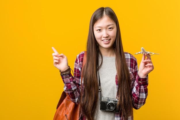 Jovem mulher asiática segurando um ícone de avião sorrindo alegremente apontando com o dedo indicador.