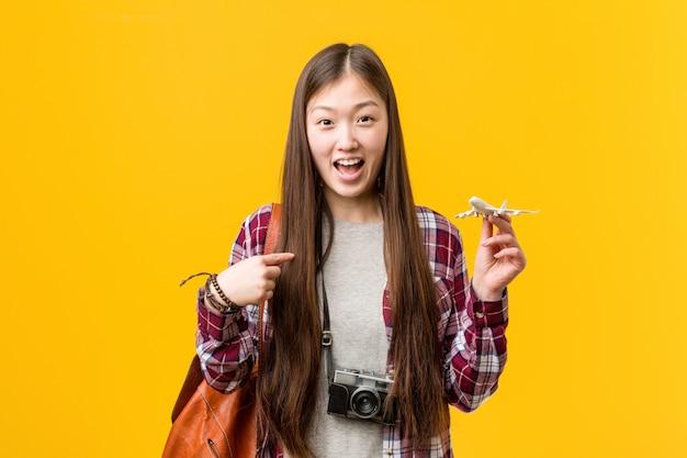 Jovem mulher asiática segurando um ícone de avião surpreendeu apontando para si mesmo, sorrindo amplamente.