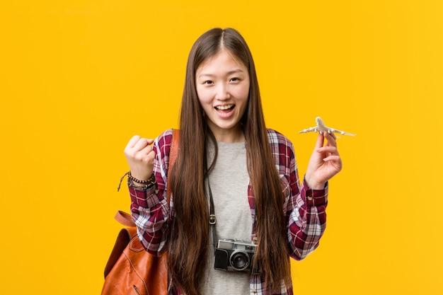 Jovem mulher asiática segurando um ícone de avião torcendo despreocupado e animado. conceito de vitória