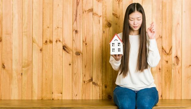 Jovem mulher asiática segurando um ícone de casa cruzando os dedos por ter sorte