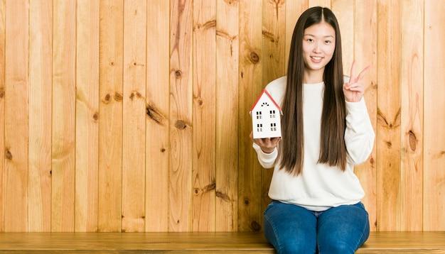 Jovem mulher asiática segurando um ícone de casa, mostrando o número dois com os dedos.