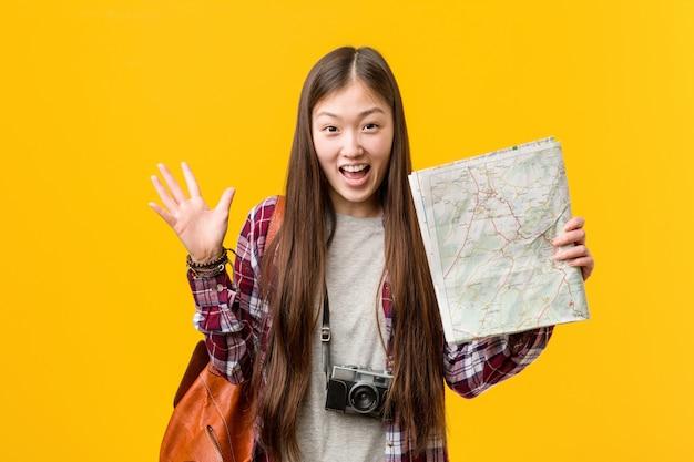 Jovem mulher asiática segurando um mapa comemorando uma vitória ou sucesso