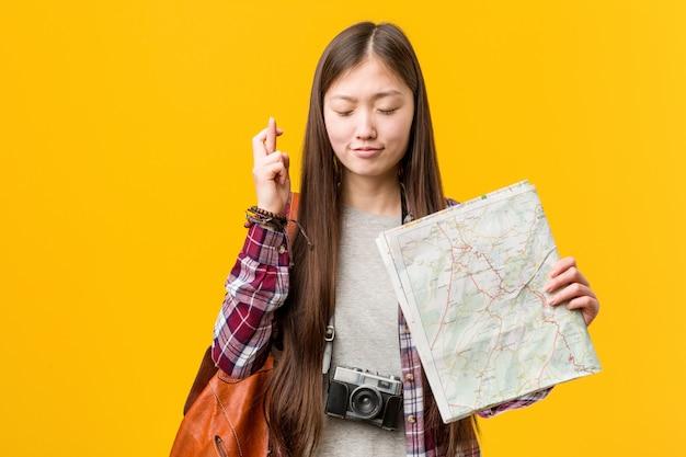 Jovem mulher asiática segurando um mapa cruzando os dedos por ter sorte