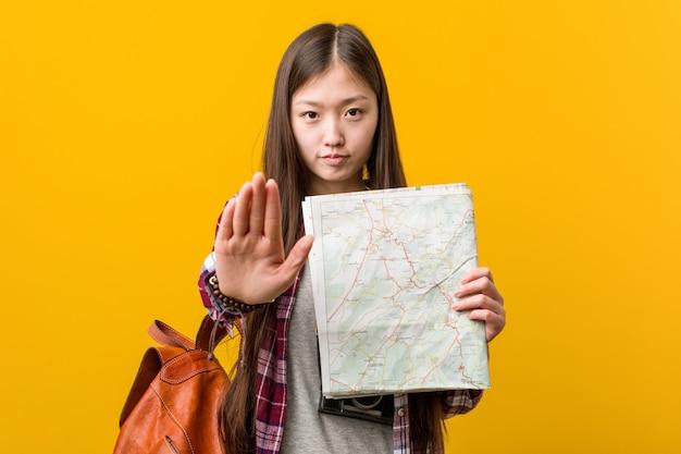 Jovem mulher asiática segurando um mapa em pé com a mão estendida, mostrando o sinal de stop, impedindo-o.