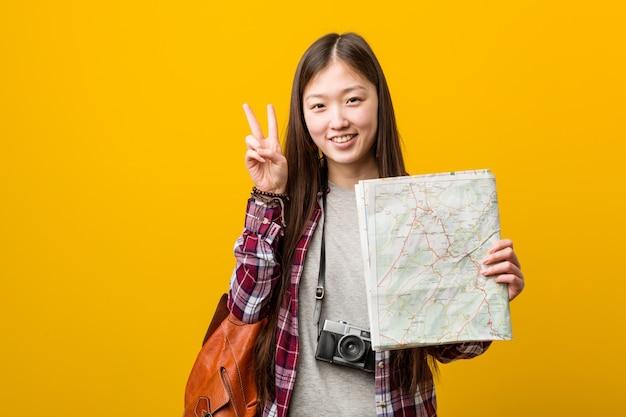 Jovem mulher asiática segurando um mapa mostrando sinal de vitória e sorrindo amplamente.