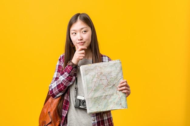 Jovem mulher asiática segurando um mapa olhando de soslaio com expressão duvidosa e cética.