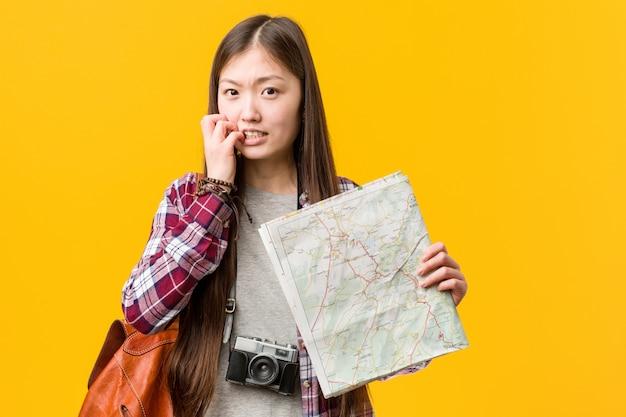 Jovem mulher asiática segurando um mapa roer as unhas, nervoso e muito ansioso.