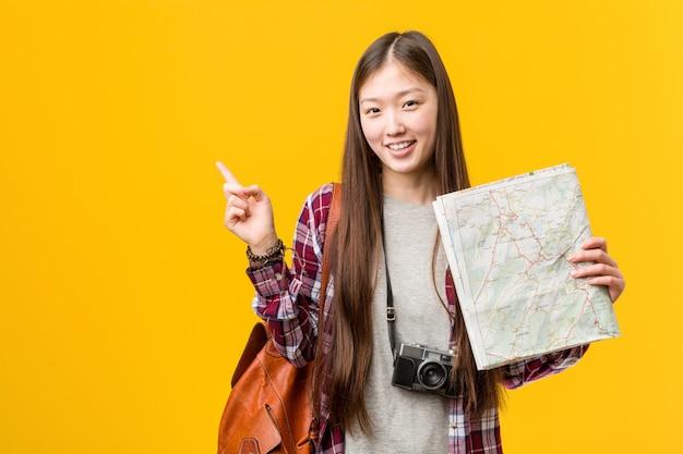 Jovem mulher asiática segurando um mapa sorrindo alegremente apontando com o dedo indicador.