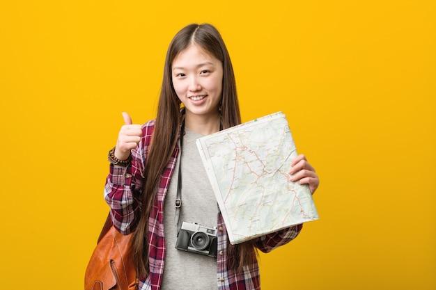Jovem mulher asiática segurando um mapa sorrindo e levantando o polegar