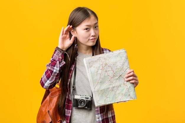 Jovem mulher asiática segurando um mapa tentando ouvir uma fofoca.