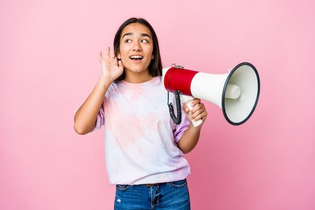 Jovem mulher asiática segurando um megafone isolado na rosa, tentando ouvir uma fofoca.