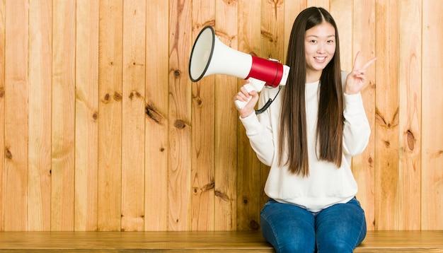 Jovem mulher asiática segurando um megafone mostrando sinal de vitória e sorrindo amplamente