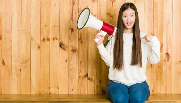Jovem mulher asiática segurando um megafone surpreendeu apontando para si mesmo, sorrindo amplamente.