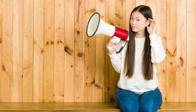 Jovem mulher asiática segurando um megafone, tentando ouvir uma fofoca.