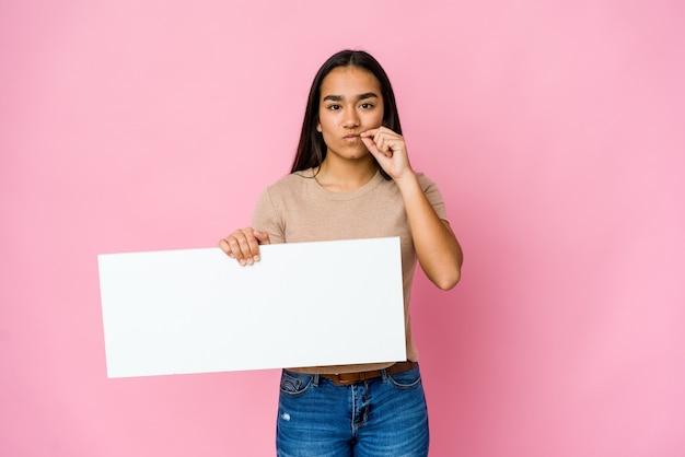 Jovem mulher asiática segurando um papel em branco para algo branco sobre uma parede isolada com os dedos nos lábios, mantendo um segredo
