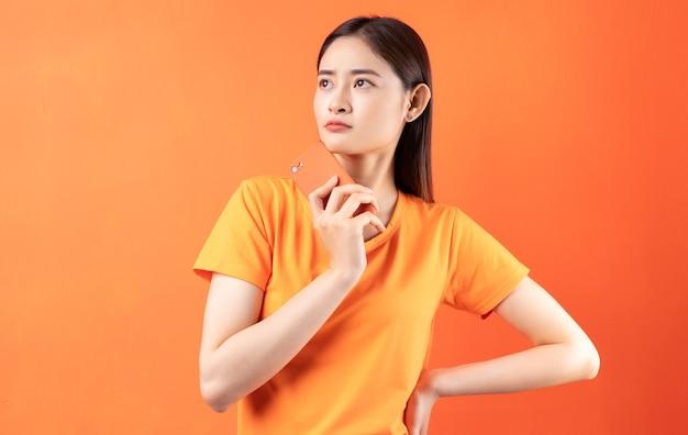 Jovem mulher asiática segurando um smartphone em laranja