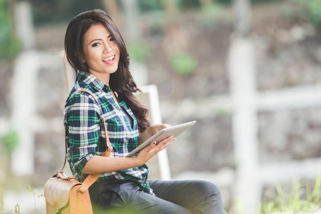 Jovem mulher asiática segurando um tablet pc enquanto está sentado no parque