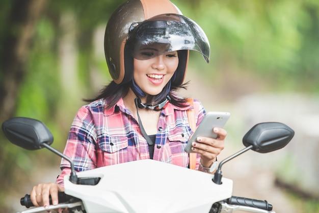 Jovem mulher asiática segurando um telefone celular enquanto está sentado em uma motocicleta
