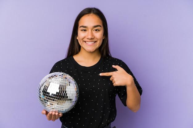 Jovem mulher asiática segurando uma bola isolada pessoa festa apontando à mão para um espaço de cópia de camisa, orgulhoso e confiante