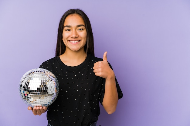 Jovem mulher asiática segurando uma festa de bola sorrindo e levantando o polegar