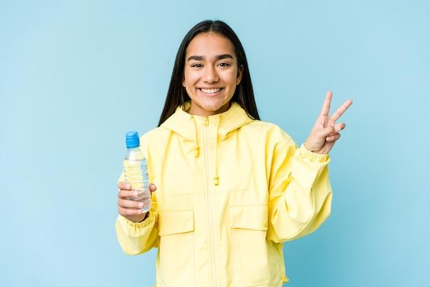Jovem mulher asiática segurando uma garrafa de água isolada no azul, alegre e despreocupada, mostrando um símbolo de paz com os dedos.
