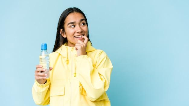 Jovem mulher asiática segurando uma garrafa de água isolada no azul relaxado pensando em algo olhando para um espaço de cópia.