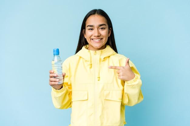 Jovem mulher asiática segurando uma garrafa de água pessoa apontando com a mão para um espaço de cópia de camisa, orgulhosa e confiante