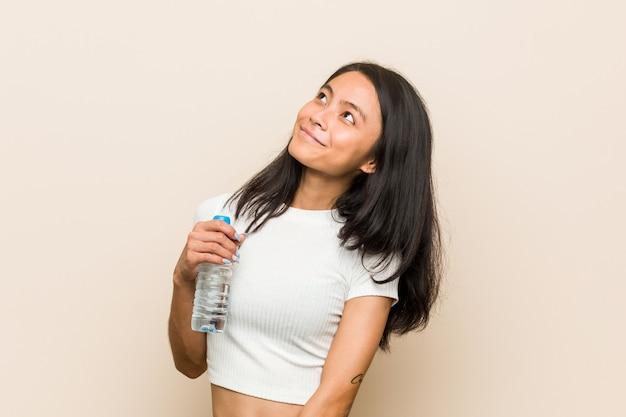 Jovem mulher asiática, segurando uma garrafa de água, sonhando em alcançar metas e propósitos