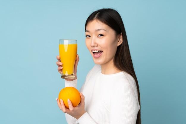 Jovem mulher asiática segurando uma laranja sobre parede azul