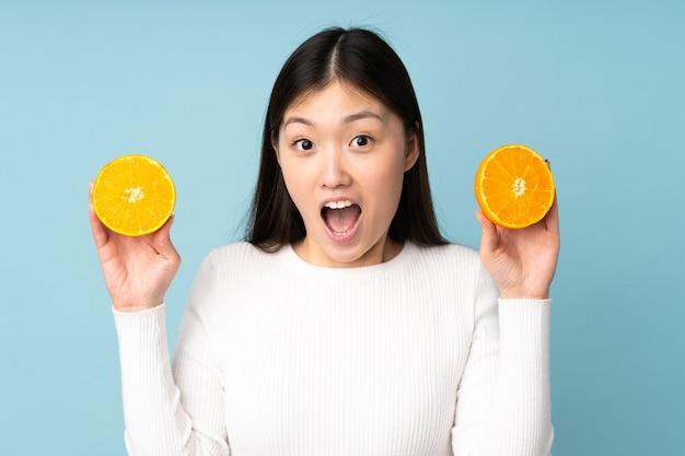 Jovem mulher asiática segurando uma laranja sobre um fundo azul isolado