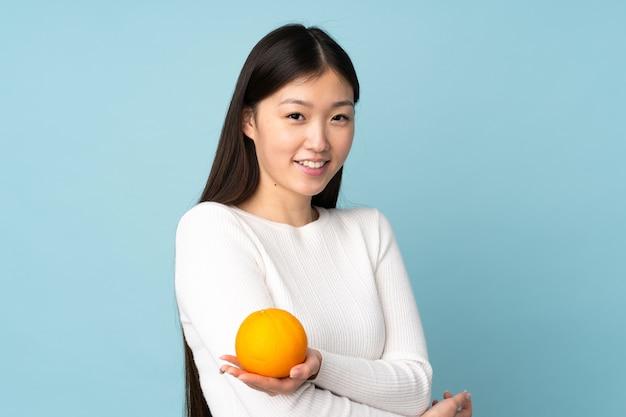 Jovem mulher asiática segurando uma laranja