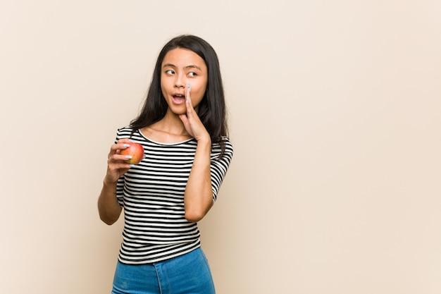 Jovem mulher asiática segurando uma maçã está dizendo uma notícia secreta sobre frenagem quente e olhando de lado