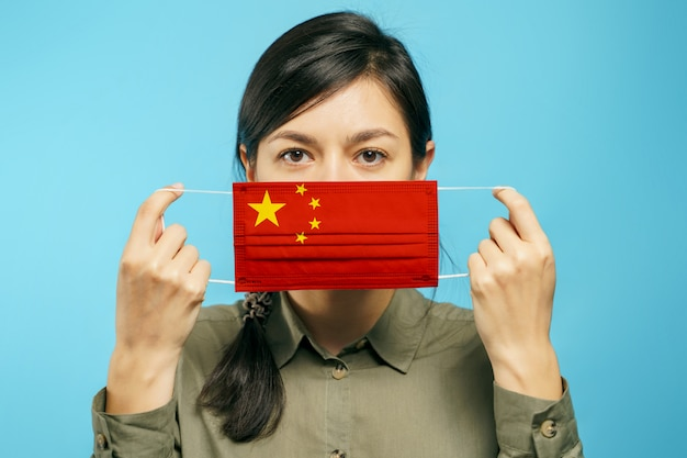 Jovem mulher asiática, segurando uma máscara de proteção médica nas mãos com a bandeira nacional chinesa em um fundo azul