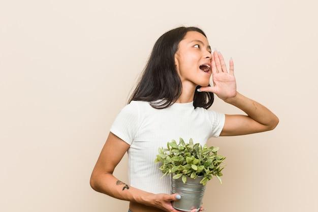 Jovem mulher asiática segurando uma planta gritando e segurando a palma perto da boca aberta.