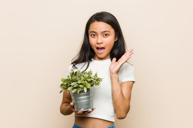 Jovem mulher asiática segurando uma planta surpreendida e chocada.