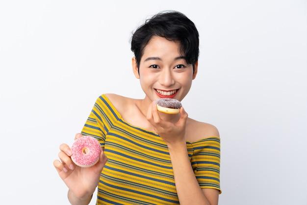 Jovem mulher asiática segurando uma rosquinha