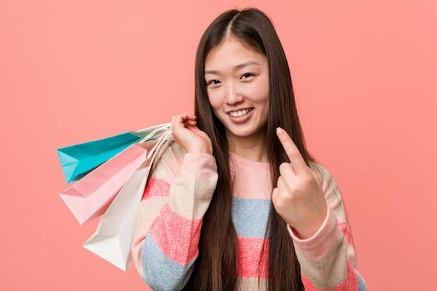 Jovem mulher asiática segurando uma sacola de compras, apontando com o dedo para você, como se convidando se aproximar.