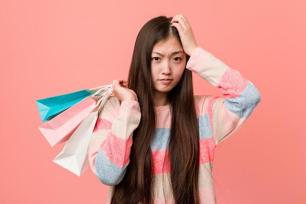 Jovem mulher asiática segurando uma sacola de compras ficar chocada, ela se lembrou de uma reunião importante.