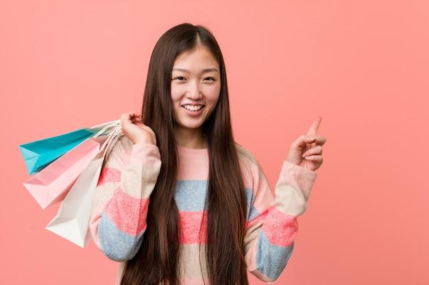 Jovem mulher asiática segurando uma sacola de compras sorrindo alegremente apontando com o dedo indicador.