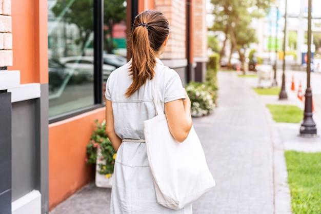 Jovem mulher asiática segurando uma sacola reutilizável e caminhando pela cidade, conceito de desperdício zero