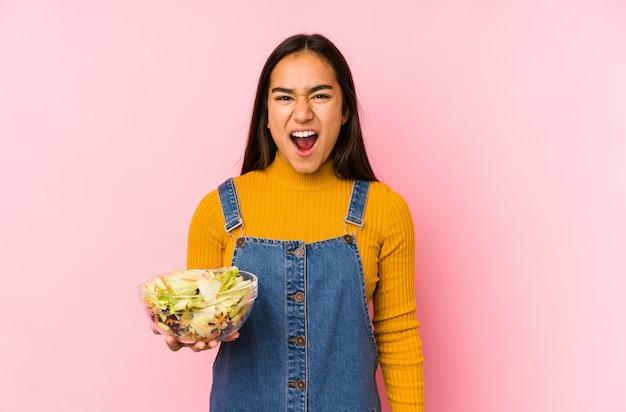 Jovem mulher asiática segurando uma salada gritando muito irritado e agressivo.