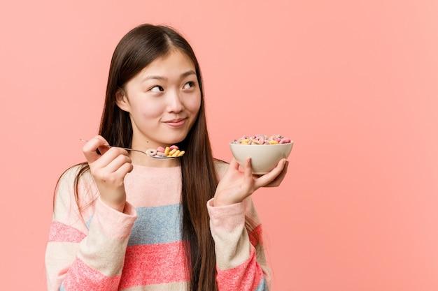 Jovem mulher asiática segurando uma tigela de cereais